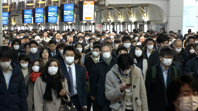 Masked crowds in Japan rush hour