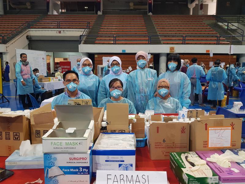 The pharmacist team at Pasir Gudang Indoor Stadium on March 18th. Back row [L-R]: Siti Rabiatul, Klinik Kesihatan (KK) Mahmodiah; Fauziah Aris and Fatimah, KK Ulu Tiram; and Chew Sin Nah, KK Masai. Front row [L-R]: Ong Aik Liang, Hospital UKM; Vivian Chuah, KK Sultan Ismail; and Dina Syafiqah, KK Mahmoodiah. (Photo credit: Ong Aik Liang)